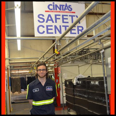 A man in a factory standing under a sign that reads Cintas Safety Center