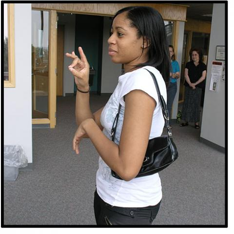 A woman uses sign language with someone off camer