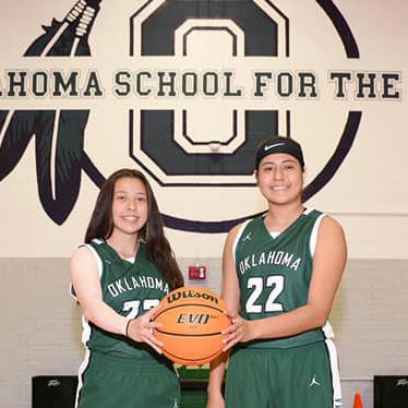 Two students hold a basketball