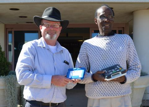 Two men hold a cartridge and audio player in front of a building