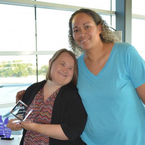 Woman hugs smiling woman with award