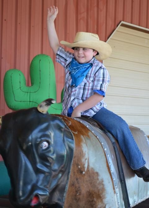 Boy wearing cowboy hat rides mechanical bull.