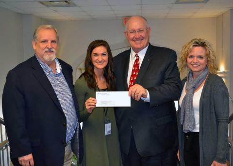 Four people in business clothes pose with a check