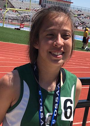 Young smiling woman wearing medal on a ribbon stands on track in stadium.