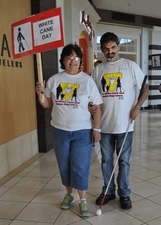 Man with white cane holds arm of woman with White Cane Day sign