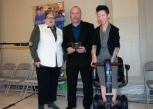 Two smiling women stand beside man holding an award.