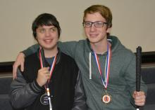 Two smiling, young men with medals around their necks and white canes