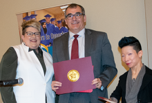 Two smiling women beside a smiling man holding a folder with a gold seal.