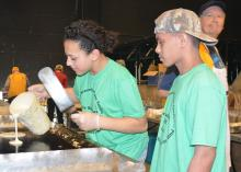 Young man watches young woman pour pancake batter from a pitcher