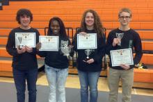 4 young people hold certificates and silver trophies.