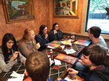 Seven people seated at restaurant table fingerspell to communicate with deaf people.