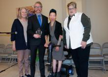 Three smiling women stand beside man holding an award.