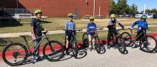 Five young people wearing helmets stand beside their bikes