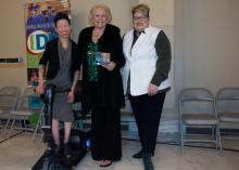 Two smiling women stand next to a woman holding an award