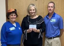 Man and woman stand beside woman holding a check.