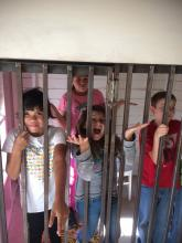 Four children stand behind bars.