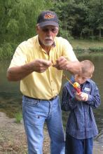 Man baits a fishing hook for a small boy