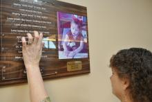 Woman reads braille on acrylic sheet over text on a wood plaque