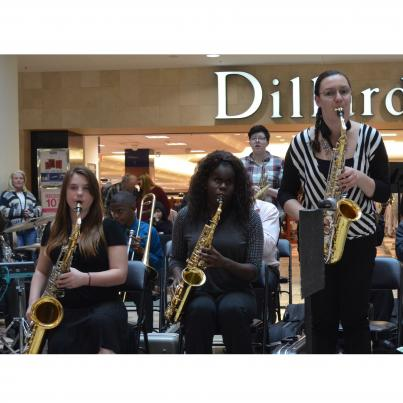 Five students play saxophones in a mall playing instruments